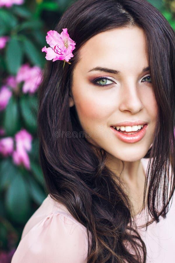 Härlig framsida av den unga kvinnan med makeup över de rosa blommorna Stående av den nätta sunda hudflickan utomhus- royaltyfria foton