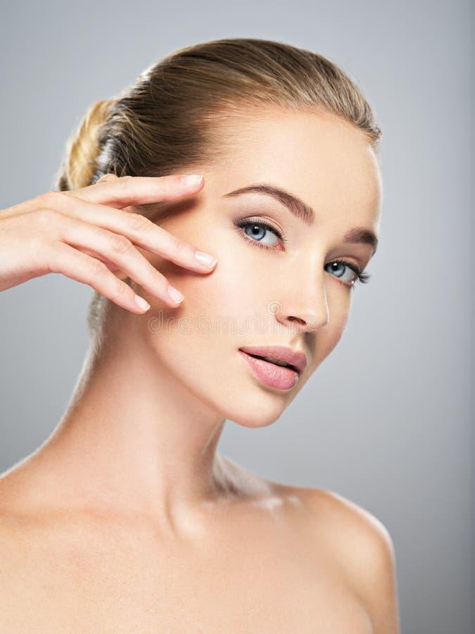 Härlig framsida av den unga kvinnan med perfekt hud royaltyfri bild