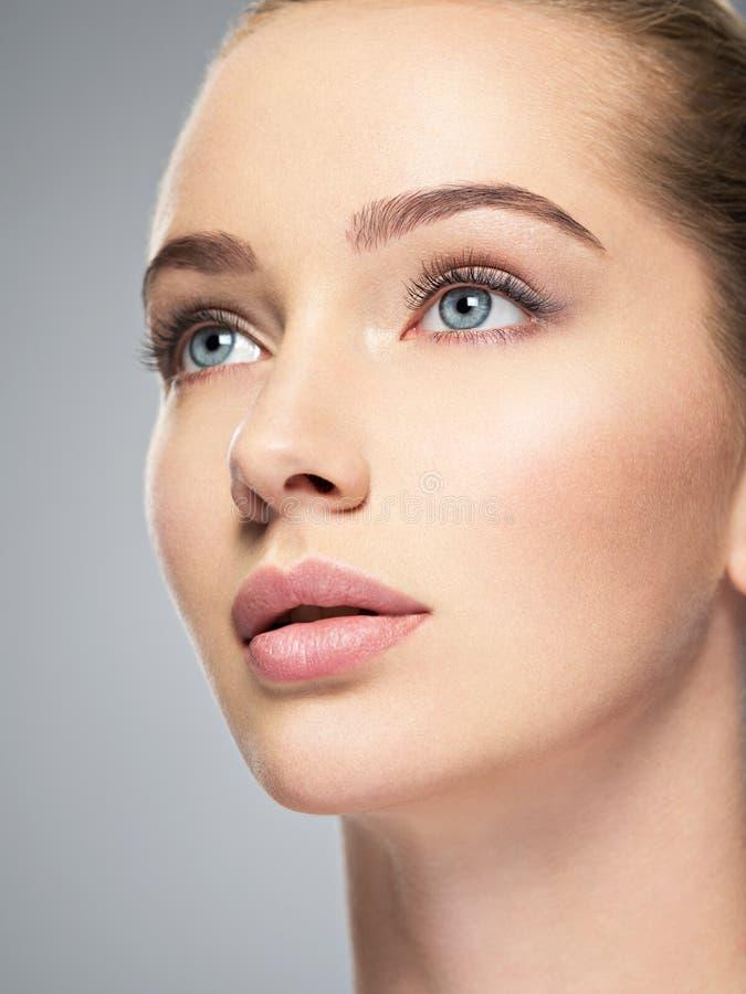 Härlig framsida av den unga kvinnan med perfekt hud arkivfoto
