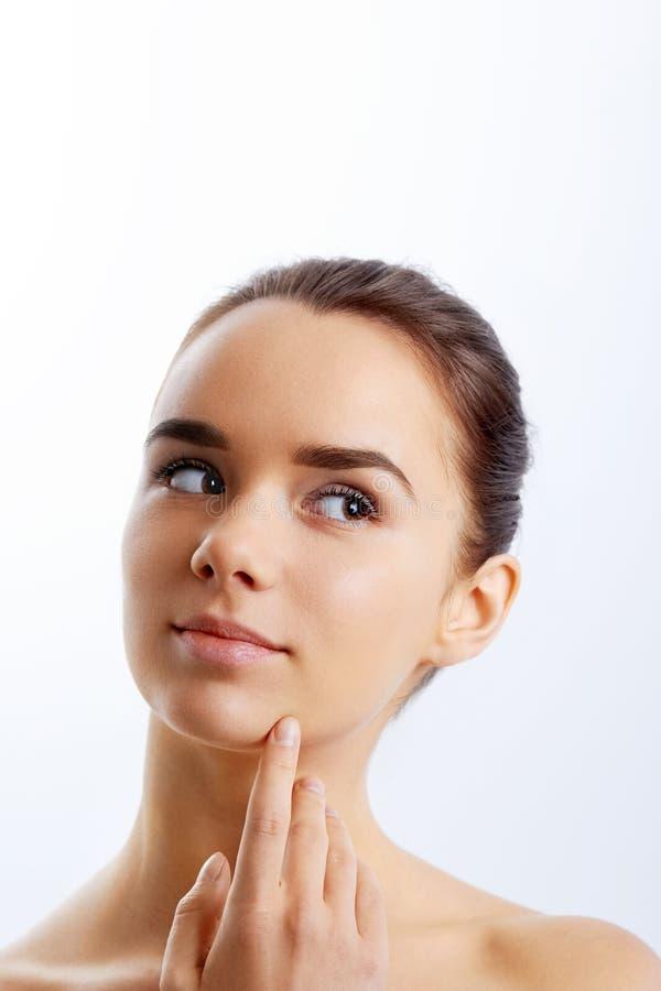 Härlig framsida av den unga vuxna kvinnan med ren ny hud applicera genomskinlig fernissa för omsorgshud moisturiser royaltyfri fotografi