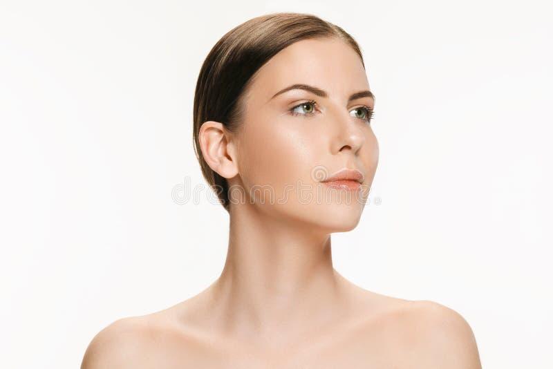 Härlig framsida av den unga vuxna kvinnan med ren ny hud som isoleras på vit arkivfoton
