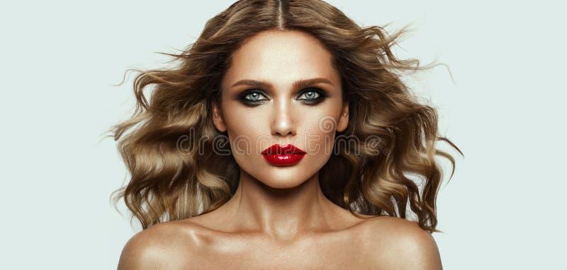 Härlig framsida av en modemodell med blåa ögon lockigt hår röda kanter royaltyfri fotografi