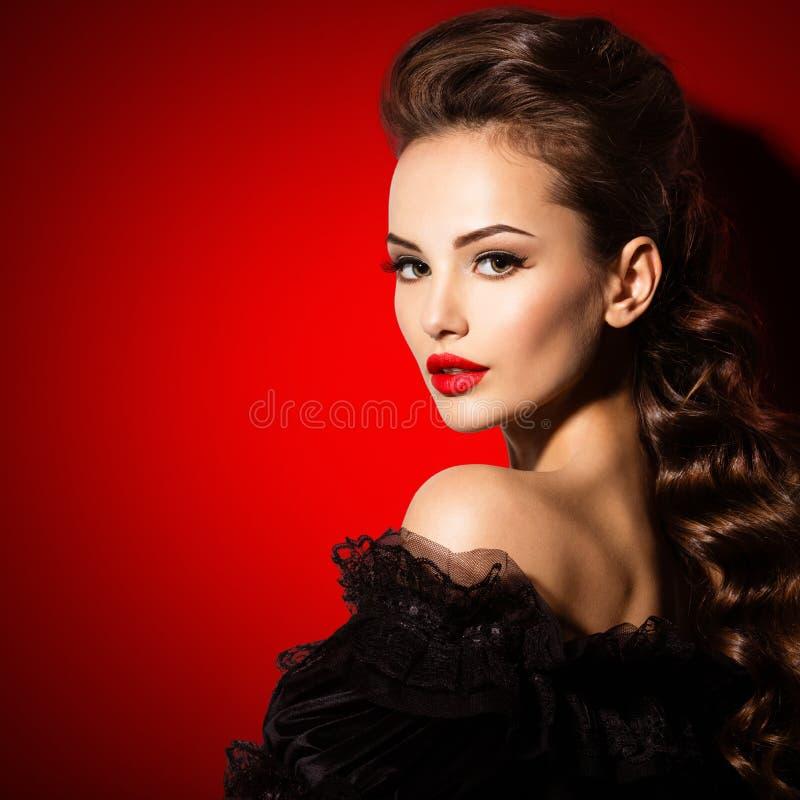 Härlig framsida av en ung sexig kvinna i svart klänning med röd läppstift royaltyfri foto