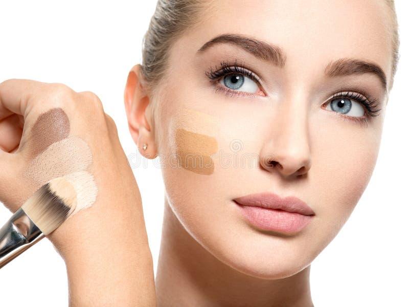 Härlig framsida av kvinnan med det kosmetiska fundamentet på en hud arkivfoton