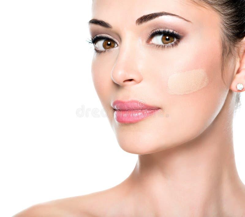 Härlig framsida av kvinnan med det kosmetiska fundamentet på en hud. arkivfoto
