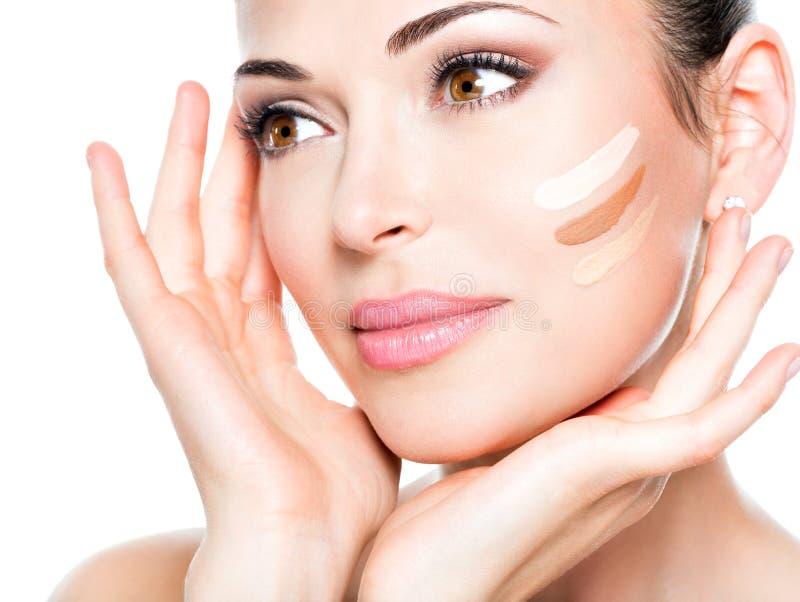 Härlig framsida av kvinnan med det kosmetiska fundamentet på en hud. royaltyfri foto