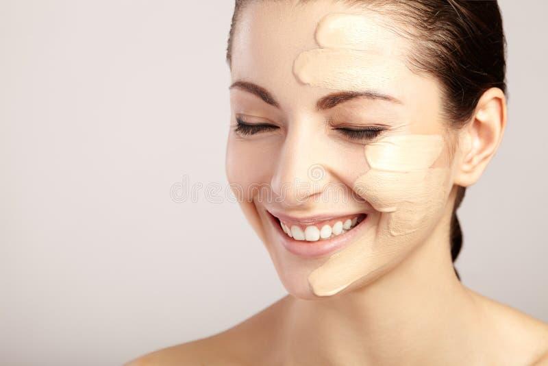 Härlig framsida av kvinnan med det kosmetiska fundamentet på hud royaltyfri fotografi