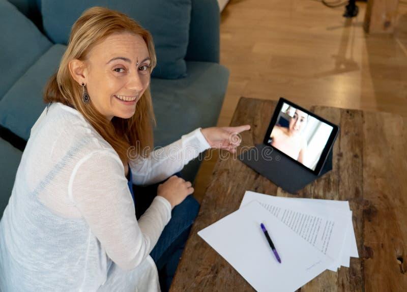 Härlig frilans- kvinnakonsulent som har en videokonferensappell med online-klienten hemma royaltyfri foto