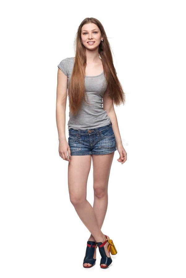 Härlig full längdkvinnlig i kortslutningar och överkant med långt hår fotografering för bildbyråer
