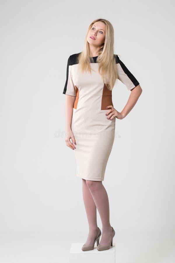 Härlig fundersam flicka i en beige klänning och skor royaltyfria foton
