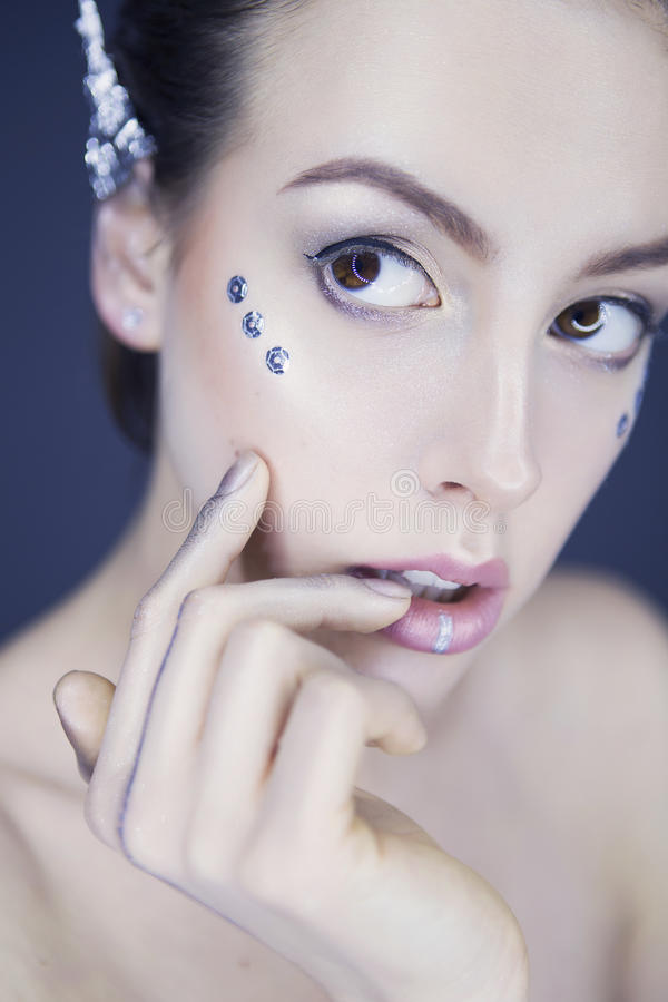 Härlig futuristisk stilsminkkvinna med folieöron och meta arkivfoton