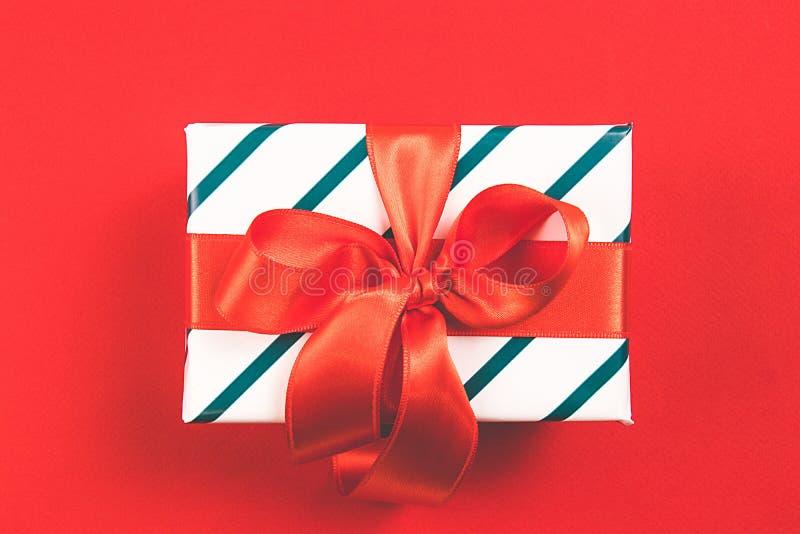 Härlig gåva med den röda satängpilbågen och som täcker i en vitbok med den gröna linjen på en röd bakgrund Festligt begrepp Top b arkivbilder