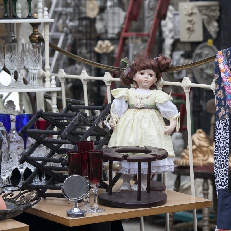 härlig gammal docka bland bohag på en loppmarknad fotografering för bildbyråer