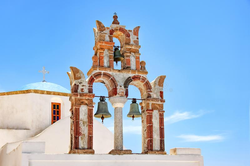 Härlig gammal ortodox vit kyrka med den blåa kupolen och den gamla bågen med klockor mot den blåa himlen, Santorini, Grekland, Eu arkivfoton