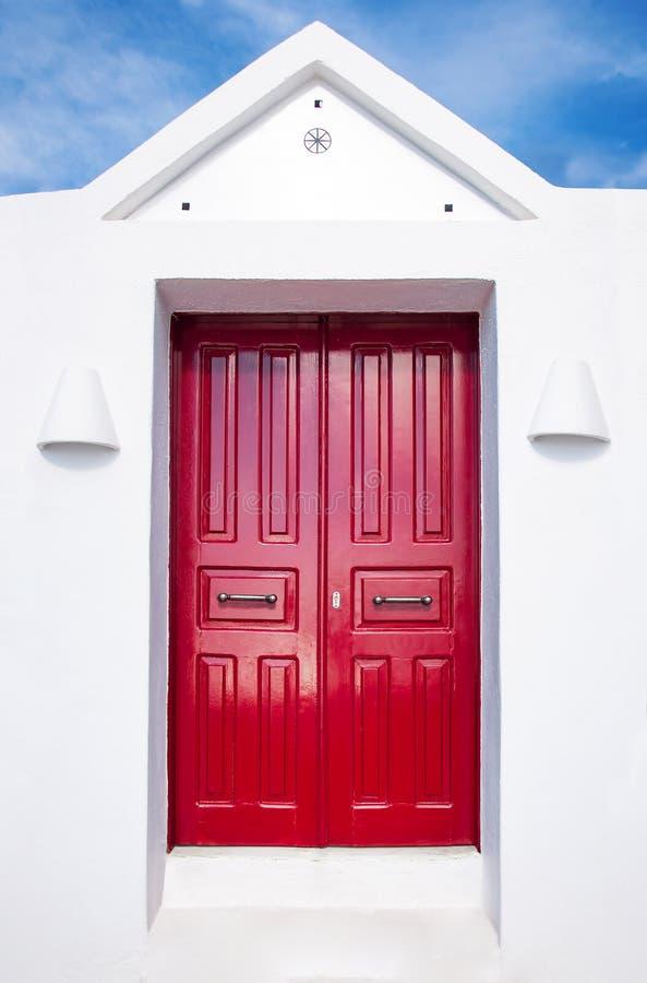Härlig gammal röd dörr på den vita fasaden av grekisk arkitektur mot den blåa himlen, Santorini ö, Grekland, Europa h?rligt arkivbilder