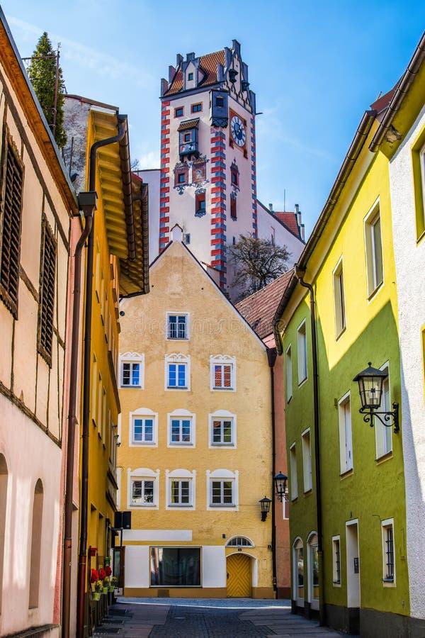 Härlig gata av gamla hus med tornet av den höga slotten royaltyfri fotografi