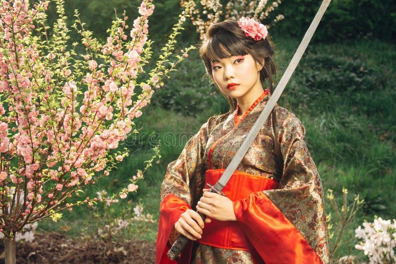 Härlig geisha i kimono med samurajsvärdet royaltyfri foto