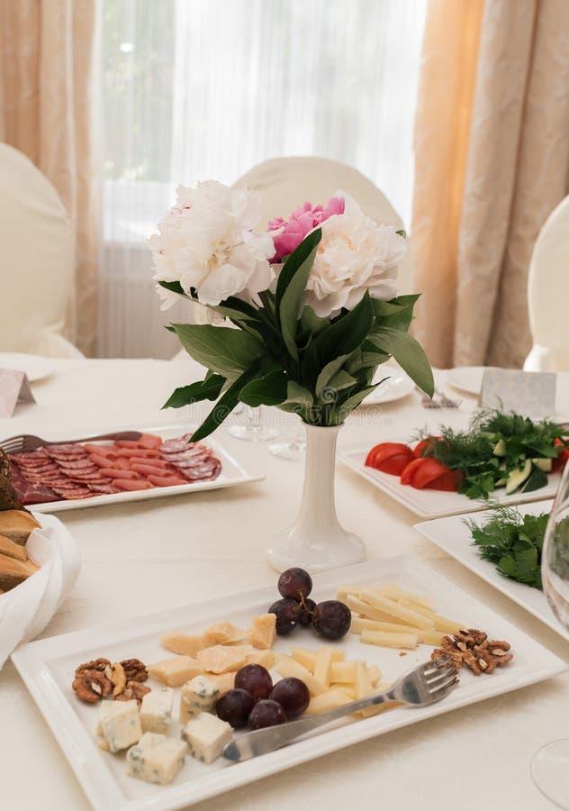 Härlig gifta sig bukett av vita och rosa pioner i den vita vasen på matställetabellen i suddighet Tabellinställning på lyxigt brö royaltyfri fotografi