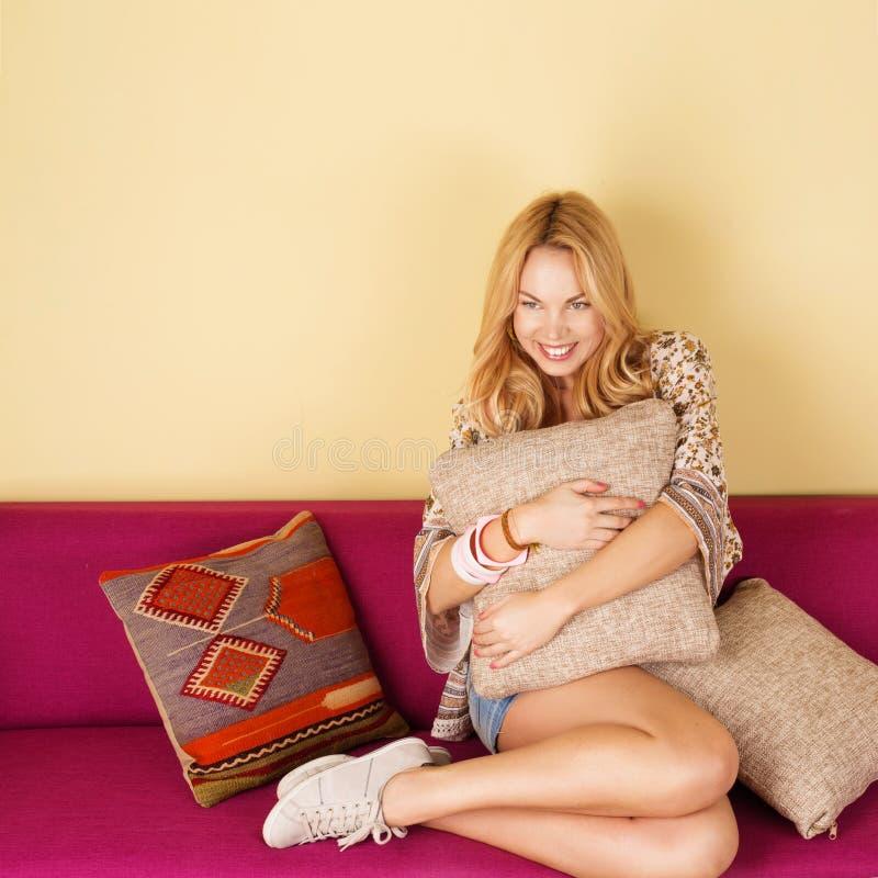 Härlig gladlynt kvinna på soffan royaltyfri bild
