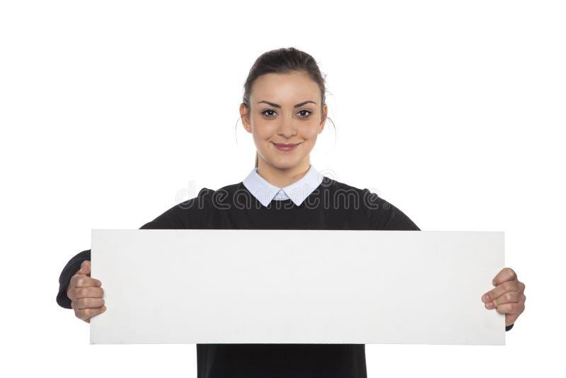 Härlig gladlynt kvinna som rymmer en tom affischtavla, kopieringsutrymme royaltyfria foton