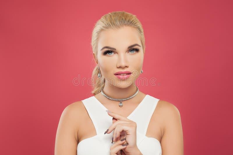 Härlig glamorös kvinna med den modesmyckenörhängen och halsbandet med diamanten och pärlor mot färgrik rosa väggbakgrund royaltyfri foto