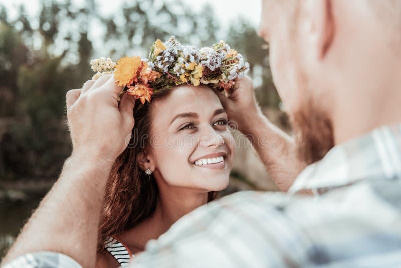 Härlig grönögd kvinna som känner den trevliga blom- chapleten för extremt lyckligt häleri royaltyfri bild