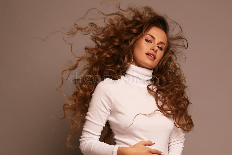 Härlig gravid flicka med mörkt lockigt hår i elegant kläder arkivbild