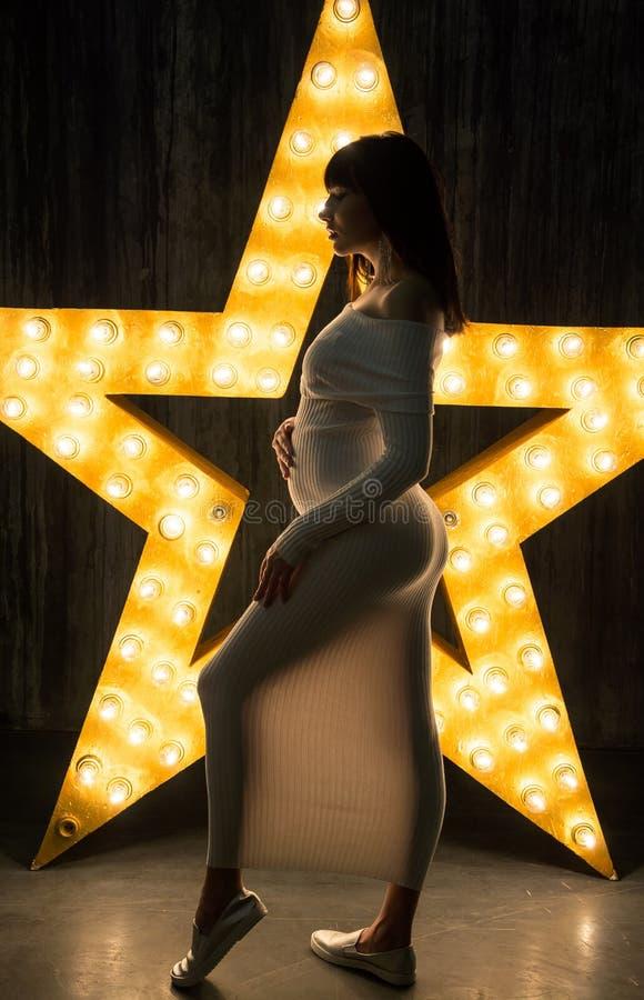 Härlig gravid kvinna framme av en glödande stjärna arkivbild