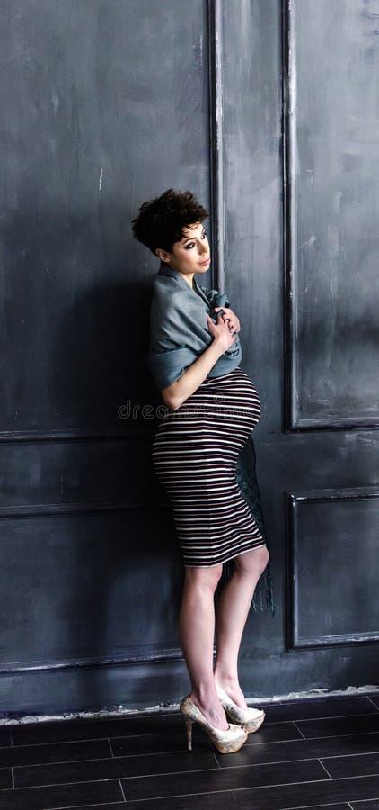 Härlig gravid kvinna hemma arkivbilder