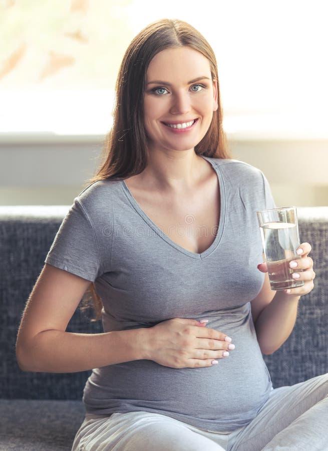 Härlig gravid kvinna hemma royaltyfri bild