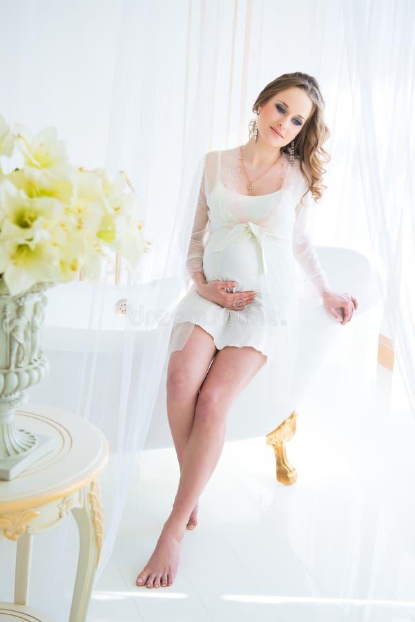 Härlig gravid kvinna i den vita underkläderna på badrummet royaltyfria foton