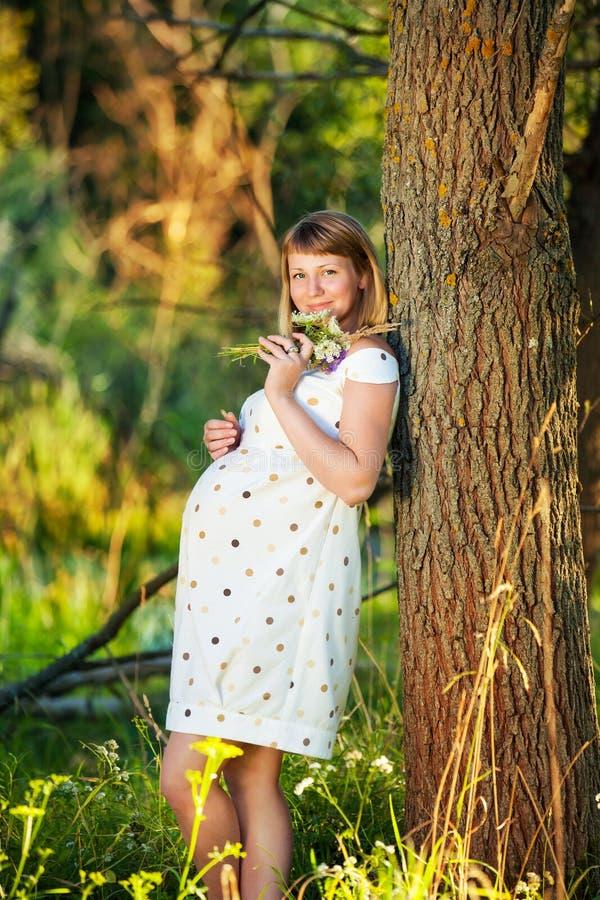 Ung gravid kvinna med utomhus- blommor royaltyfri fotografi
