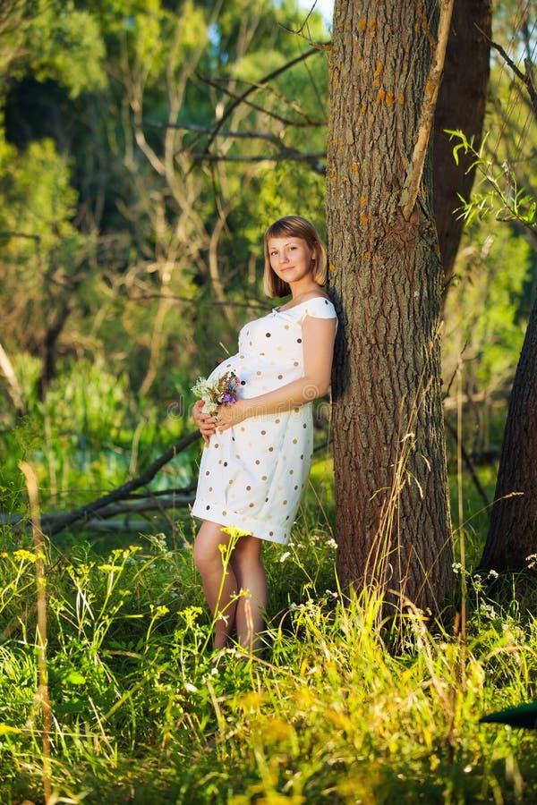 Ung gravid kvinna med utomhus- blommor royaltyfri foto