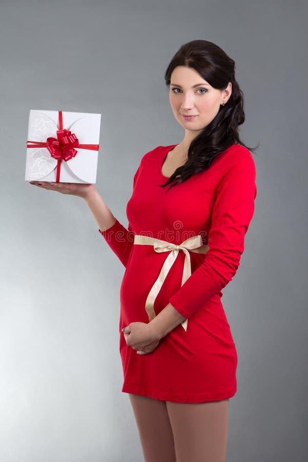 Härlig gravid kvinna i röd klänning med gåvaasken över gråa lodisar royaltyfria bilder