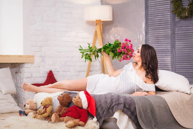 Härlig gravid kvinna i säng med rosa färgblomman arkivbilder
