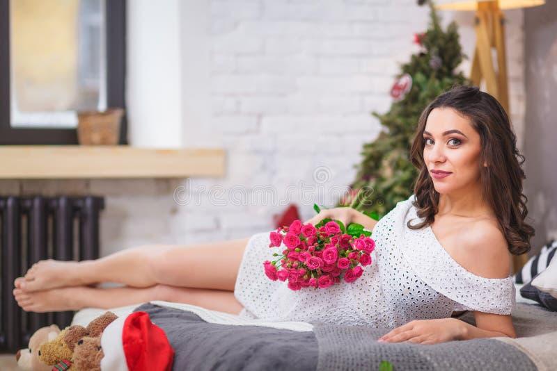 Härlig gravid kvinna i säng med rosa färgblomman royaltyfri bild