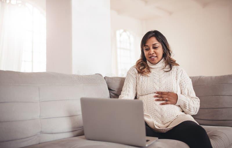 Härlig gravid kvinna med bärbar datorsammanträde på soffan fotografering för bildbyråer