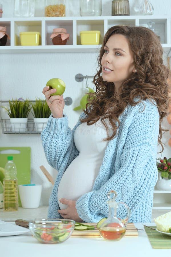 Härlig gravid kvinna med mat arkivbild