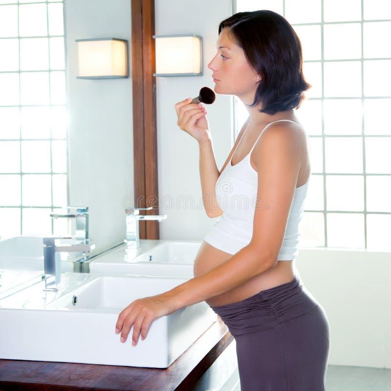 Härlig gravid kvinna på modern badrummakeup arkivfoto