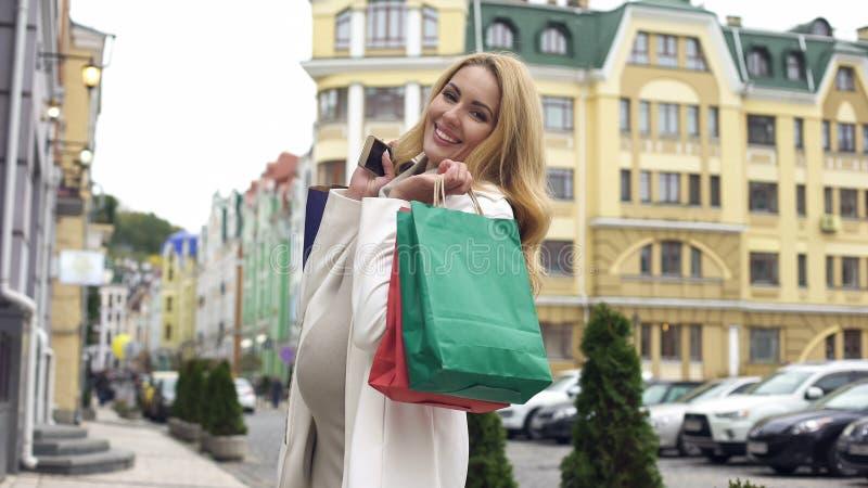 Härlig gravid kvinna som in camera ler och att rymma shoppingpåsar och smartphonen arkivfoto