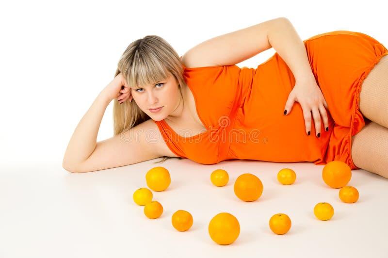 Härlig gravid kvinna som ligger med apelsiner royaltyfri bild