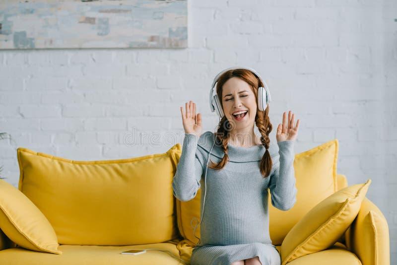 härlig gravid kvinna som lyssnar till musik och att dansa royaltyfria bilder