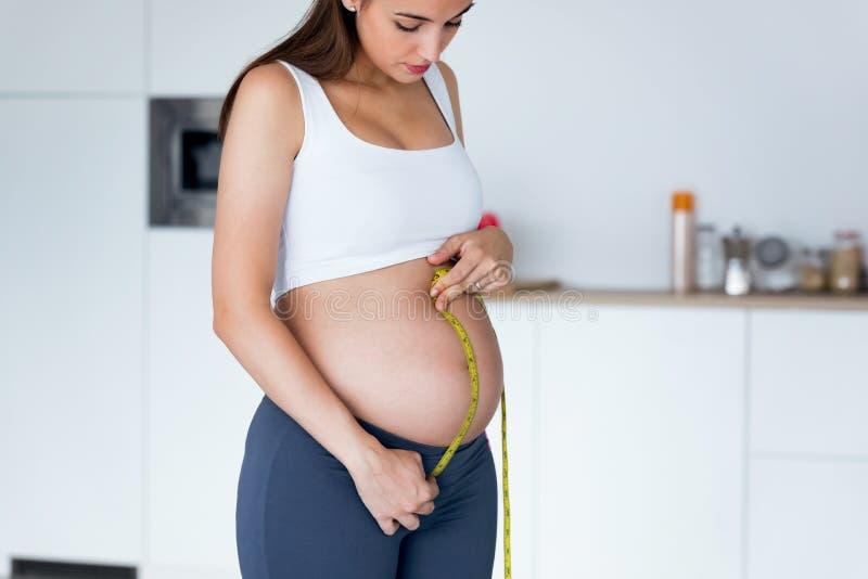 Härlig gravid kvinna som mäter hennes buk med ett band för att hålla spåret av hennes fosterutveckling Sunt havandeskapbegrepp arkivbild