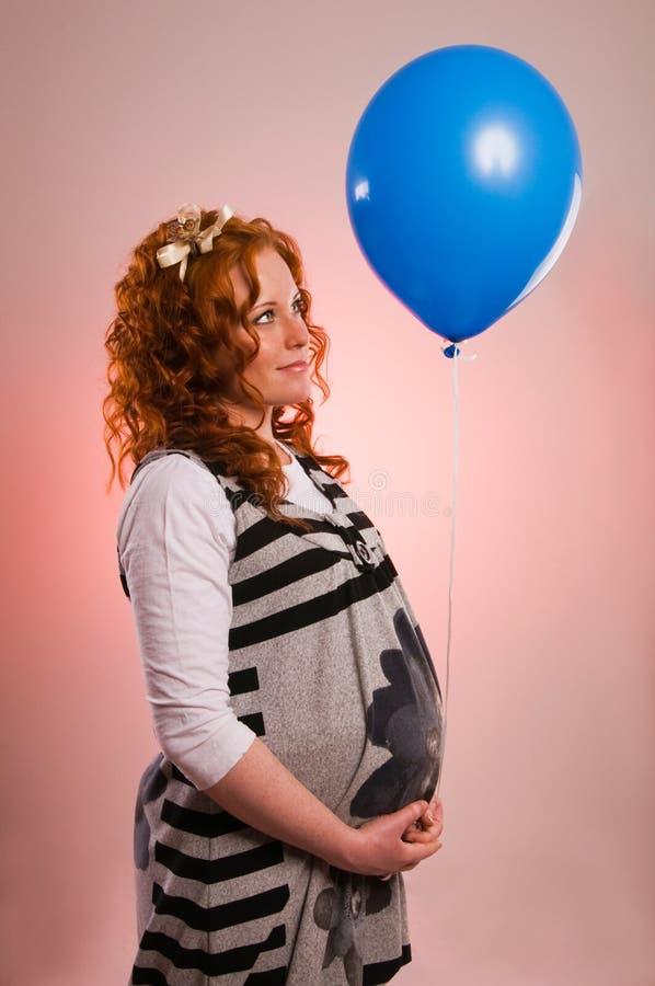 Härlig gravid kvinnaholdingballong arkivbild