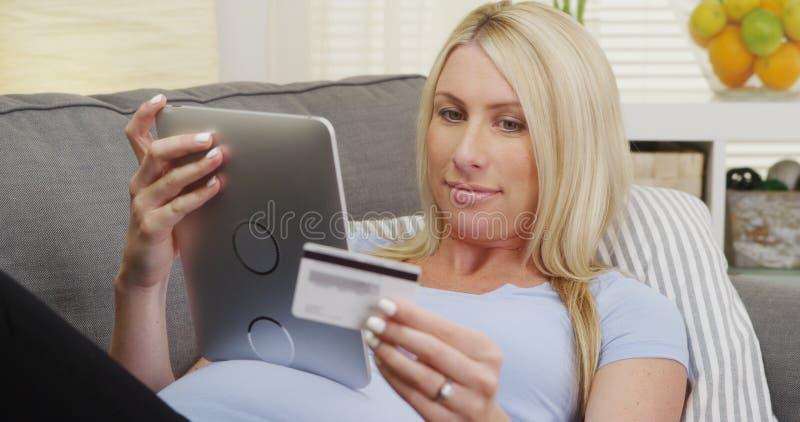Härlig gravid kvinnaköpande behandla som ett barn tillförsel direktanslutet royaltyfri bild