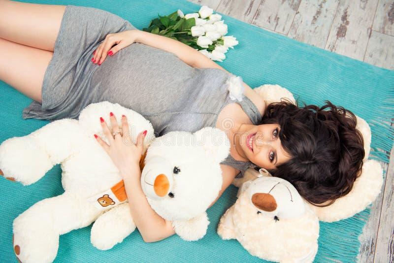 Härlig gravid moder med nallebjörnar royaltyfria bilder