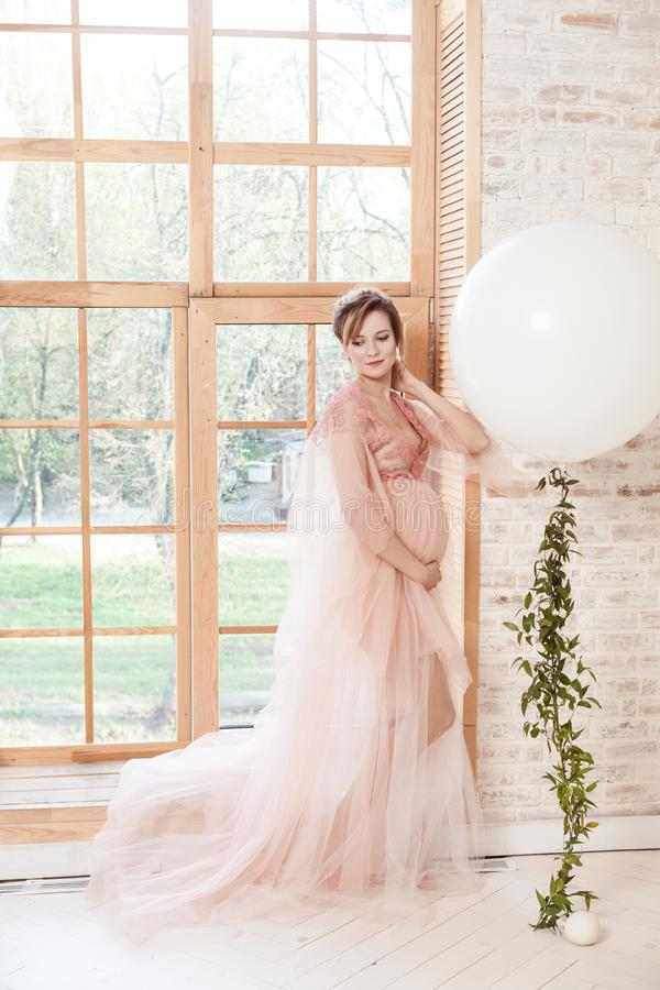 Härlig gravid ung kvinna, i rosa klänninganseende nära stort naturligt fönster och att trycka på hennes hals med handen royaltyfri bild