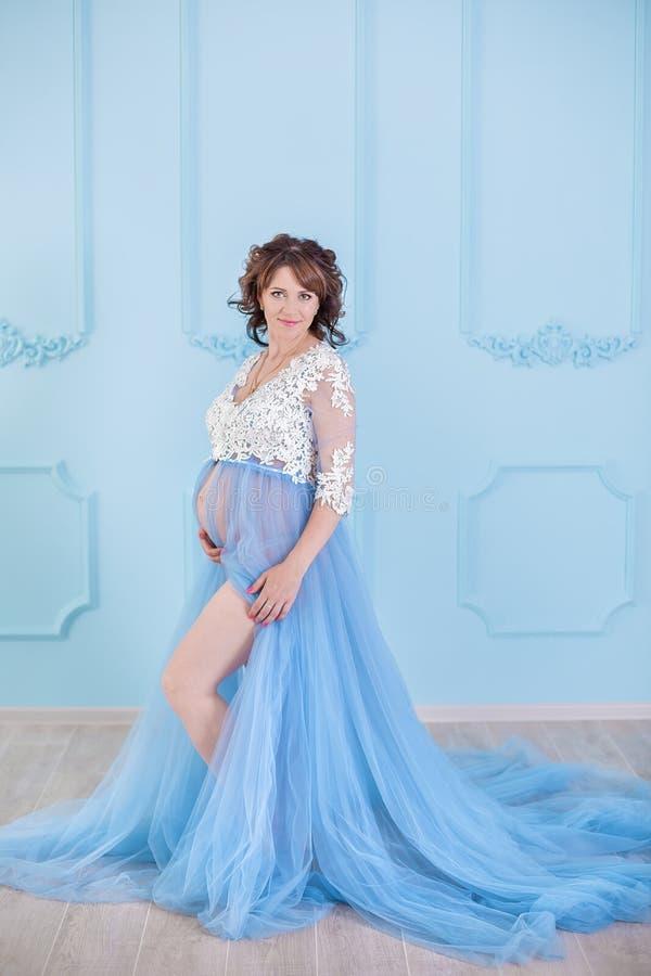 Härlig gravid ung kvinna som bär den lyxiga blåa damunderkläderklänningen, studiostående av att förbluffa damen med lockiga brune royaltyfri foto
