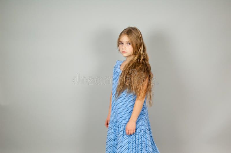 Härlig grundskola för barn mellan 5 och 11 årflicka med långt mörkt hår - på grå bakgrund arkivbild