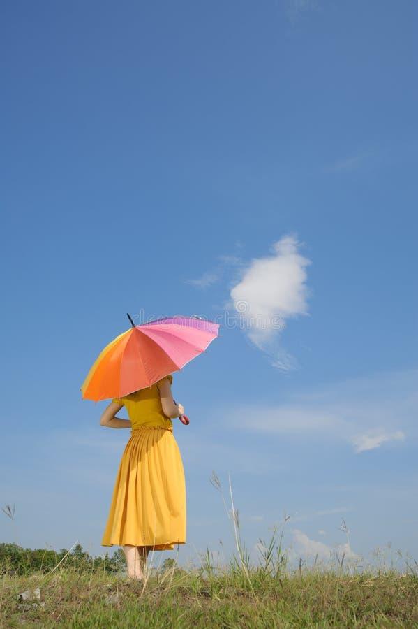 Härlig gul kvinna som rymmer mångfärgad paraply- och molnhimmel royaltyfria foton